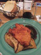 Chicken schnitzel with a side of pierogies, braised greens, onion gravy